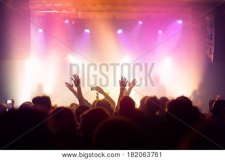 Music concert crowd fans people at popular live rock performance hands in the air selective focus