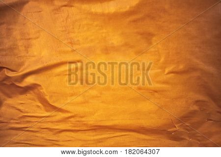 Golden yellow glued poster paper background creased and crumpled surface