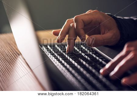 Computer programmer and hacker hands typing laptop keyboard close up low key with selective focus
