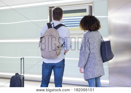 Young couple checking the timetable on a station for a train