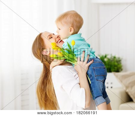 Happy mother's day. Baby son congratulates mom gives her flowers