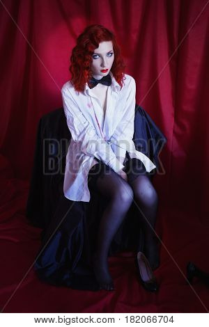 Woman with long red curly hair in white unbuttoned shirt and black bow tie and stockings on red background. Red-haired girl with pale skin unusual appearance red lips. A prostitute burlesque model