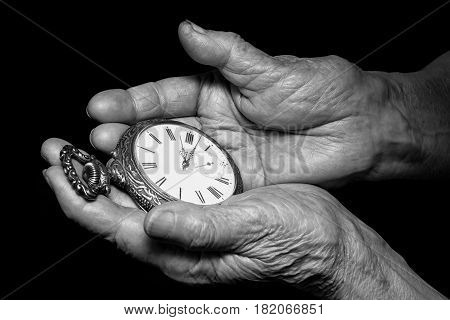Senior woman hands holding ancient clock. Aging problems senior age and stream of time theme. Black and white photo on black background