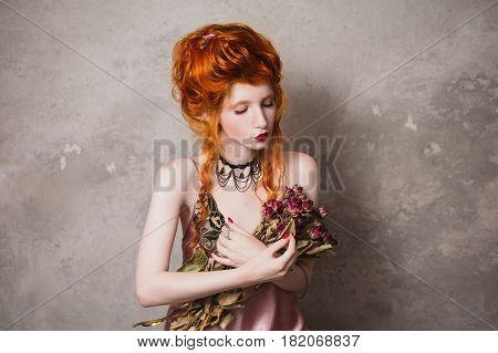 A woman with red hair in a nightgown. Red-haired girl with pale skin and blue eyes with bright unusual appearance with choker around her neck with a bouquet of dried roses. French courtesan. Copyspace