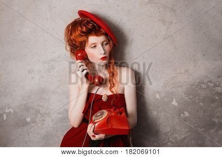 A vintage woman with red hair in a red dress. Red-haired vintage girl with pale skin and blue eyes with a bright unusual appearance with vintage beret on her head on a gray background. French courtesan. Art vintage photo