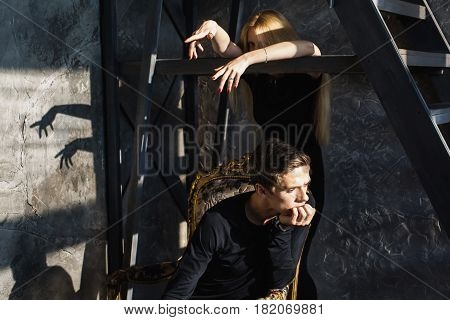 A young unhappy man and young blonde woman with long hair. Problems and difficulties in relations. Difficult unhappy situation in life. Conceptual unhappy photography. Actor play. Hard shadows. Show feelings. Hide feelings.