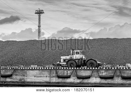 Tractor at coal pile coal shipping terminal.