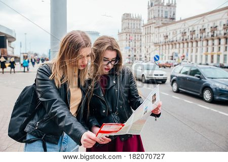 Happy travel together of two fashionable girls in sunny city centre. Young joyful women expressing positivity, using map, vacation