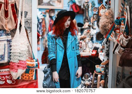 Woman with red curly hair in a blue coat against the background of souvenir shop. Red-haired girl with pale skin and blue eyes and bright unusual appearance with black hat on head and bag on shoulder