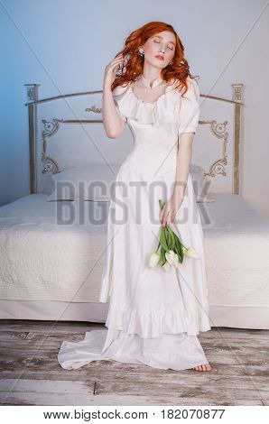 Elegant woman with long red curly hair in white vintage elegant wedding dress with white pearl earrings on ears. Red-haired elegant girl with pale skin blue eyes unusual appearance in the bedroom with white tulips in hands. Elegant model