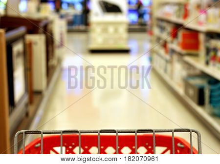 Photo of red shopping cart facing electronics aisle at store.