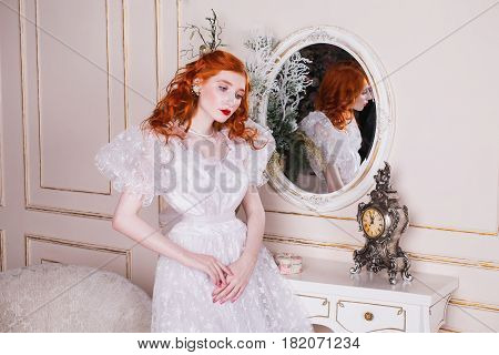 Gorgeous woman with long red curly hair in a white vintage gorgeous wedding dress with white pearl earrings on her ears. Red-haired gorgeous girl with pale skin blue eyes a bright unusual appearance in the luxurious bedroom. Gorgeous model