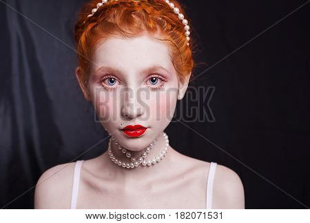 Woman with long red hair pinned on her head a necklace of beads on a black background. Red-haired girl with red lips pale skin blue eyes a bright unusual appearance in a white dress. White beads. Necklace of beads. Beads on the head. Beads around the neck