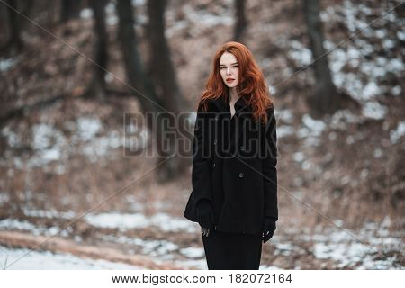 Striking casual girl with long red hair in black clothes. A casual woman in a black coat posing on a background of winter autumn nature. Female street casual fashion style. Beautiful elegant redhead model.