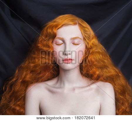 Woman with long curly red flowing hair on a black background. Red hair girl with pale skin blue eyes bright unusual appearance without makeup. Natural beauty. The girl from the era of renaissance with long hair. Red hair model. Lush hair