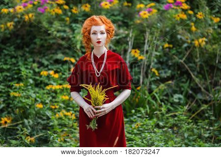 A woman with red hair and a red slinky dress with a bouquet of yellow flowers in hand in park. Red-haired girl with pale skin blue eyes and bright unusual appearance with a necklace of beads around her neck in park. Model in park