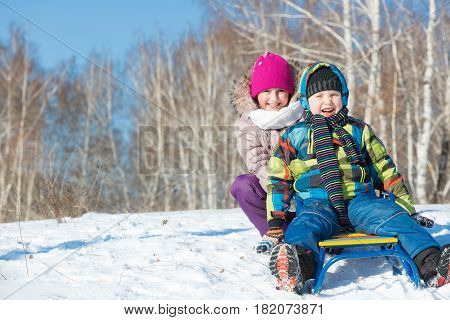 Two cute kids riding sled and having fun