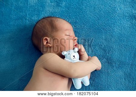 newborn baby laying asleep with a toy blue soft teddy bear on the bed on her back