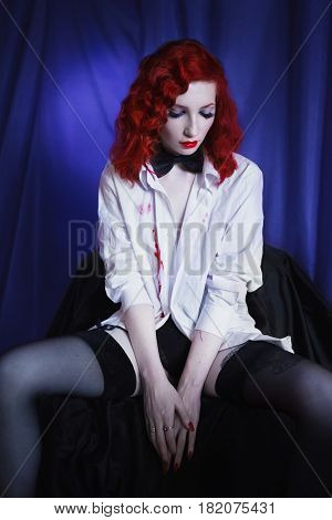 Provocative woman with long red curly hair in white unbuttoned shirt and black bow tie and stockings on blue background. Red-haired girl with pale skin unusual appearance red lips. A prostitute burlesque provocative model