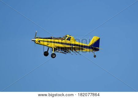 A small crop duster is flying in the sky near Spangle Washington.