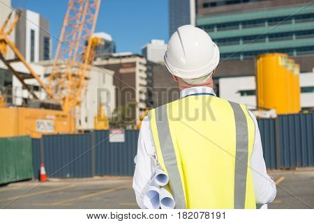 Back view of construction engineer in hardhat looking at building