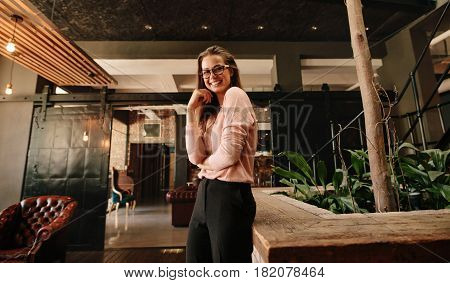 Portrait of beautiful young woman looking at camera and smiling. Business woman in office lobby looking happy.