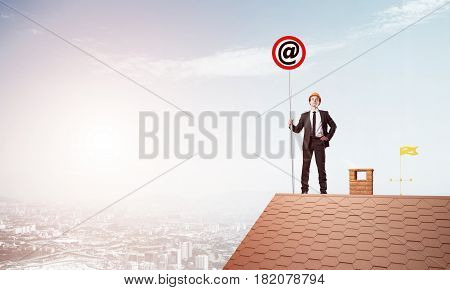 Young businessman on house roof with roadsign in hand. Mixed media
