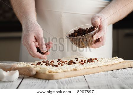 Closeup Of Man Adds Raisin Into Dough.