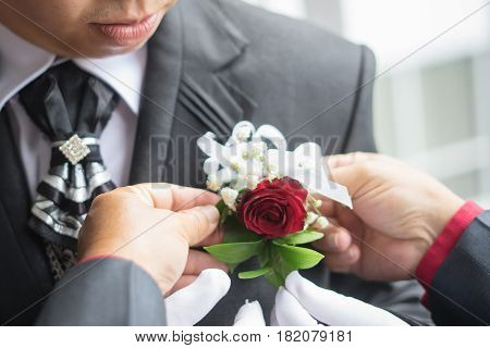 Closeup photo of bride adjusting boutonniere corsage with clematis on grooms jacket suite