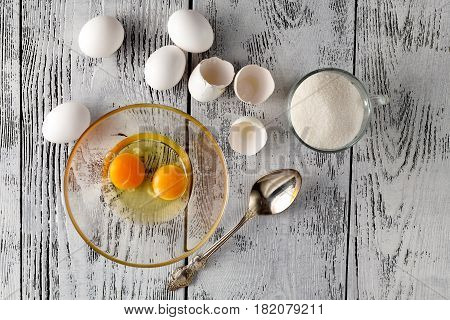 Separated Egg White And Yolks Into Two Bowls And Broken Egg Shells Are At Background