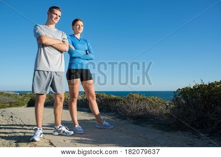 Young active couple of joggers on beach taking breath