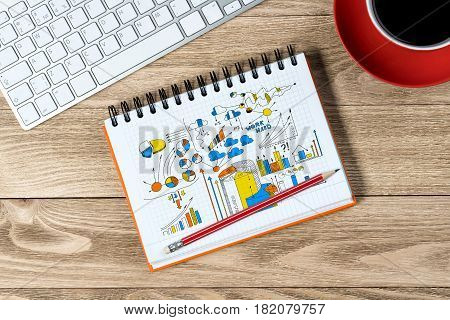 Notepad with idea sketches coffee cup keyboard and pencil on wooden table
