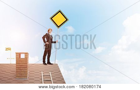Man in suit and helmet holding yellow sign on stick. Mixed media