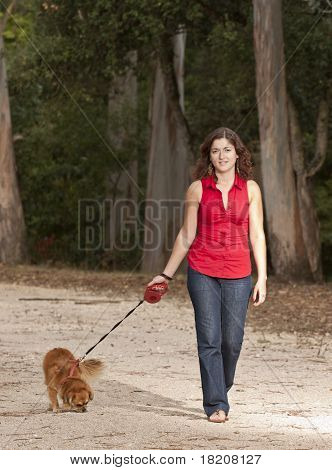 Girl With Dog Walking On The Park.
