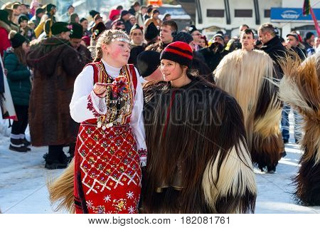 Razlog, Bulgaria - January 14, 2017: Girls in traditional carnival kuker costumes at Kukeri festival Starchevata