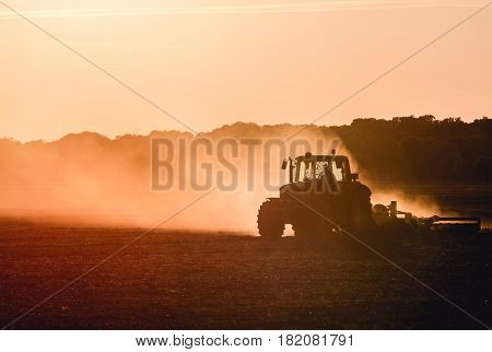 Silhouette of tractor working on a farm at twilight