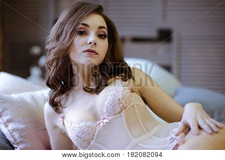 Female portrait of cute lady in pink bra indoors. Close up beautiful sexy model girl in elegant pose. Closeup beauty brunette woman with hairstyle