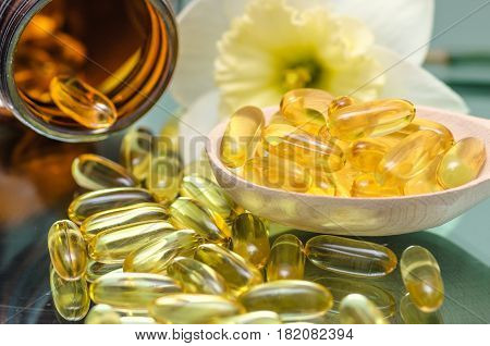 Fish oil capsule and wooden spoon with flower background. Fish oil dietary supplement.