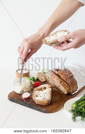 Bread with salt butter cucumber and radishes lie on a cutting wooden board on a white background. A girl is buttering a sandwich.