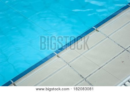Swimming pool with clear blue water and white tiles. triangle form.