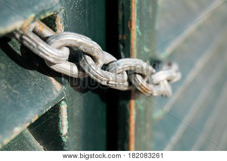 Strong chain on an old green gate.