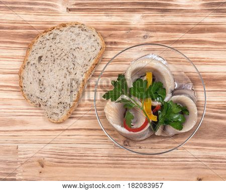 Matjes herring fillets in oil with parsley on clear plate and bread placed on wooden vintage tray