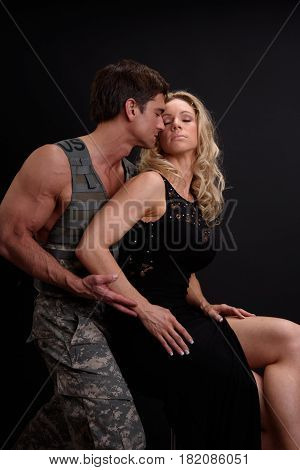 The handsome marine is putting his lady in an embrace.