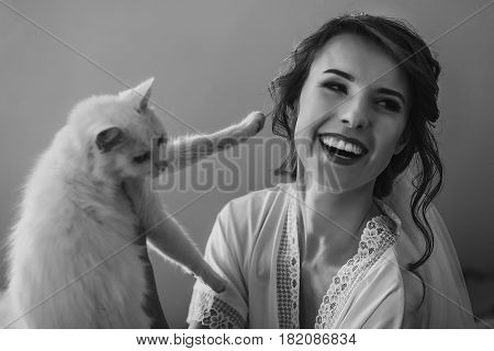 happy stylish bride in silk robe and veil playing with white cat and having fun smiling. rustic wedding morning preparation in home. space for text. luxury bride. emotional moment. black white