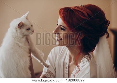 happy stylish bride in silk robe and veil playing with white cat and having fun smiling. rustic wedding morning preparation in home. space for text. luxury bride getting ready. emotional moment