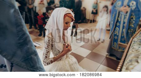 stylish bride praying during matrimony wedding ceremony in church. emotional moment space for text. religion unity concept . spiritual couple