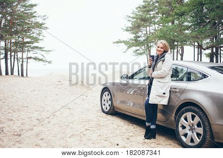 Happy woman is standing next to her car, relaxing after road trip adventure travel and drinking hot cup of take-away coffee