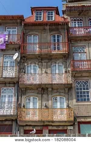 Porto, Portugal. April 17, 2017: The typical colorful buildings of the Ribeira District with the popular shops, restaurants and bars built in the stone wall. Unesco World Heritage Site.