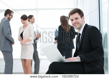 Portrait of a smiling business man sittingwith colleagues workin