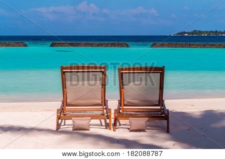 Two wooden sun loungers at the beach in Maldives